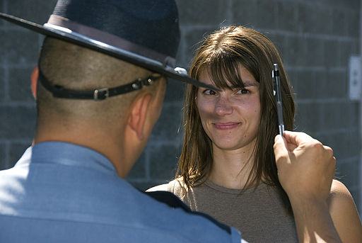 Officer giving a field sobriety test to a brunette woman
