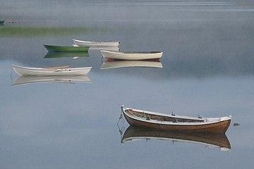 Five fishing boats on quiet misty lake.jpg