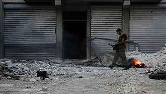 Combat operations in 2012 during the Battle of Aleppo - Free Syrian Army fighter walking among rubble in Aleppo.