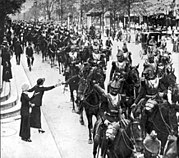 A long row of heavy cavalry stretches down a street, taking up most of the space. A woman in the foreground is reaching out and giving flowers to one of the men. They are wearing plate armor around the chest, and a crested hat on top.