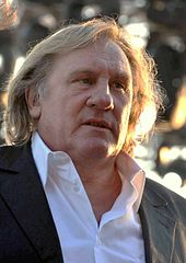 A man with long hair in an open-necked white shirt and grey jacket