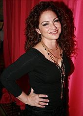A woman with curly brown hair is standing in front of a red curtain. She is sporting a black dress and a bunch of golden chains are hanging from her neck. Her hand is placed on her waist.