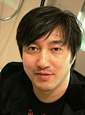 A head shot of a Japanese man in a black t-shirt.