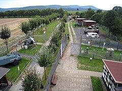 Erhöhte Ansicht einer Reihe von Hütten und Fahrzeugen, die im Freien auf beiden Seiten einer Betonpatrouillenstraße ausgestellt sind, mit einer Reihe bewaldeter Hügel im Hintergrund.