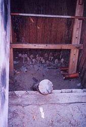 Grubehus rekonstrueret i Gene oldtidsby, Örnsköldsvik.   Til venstre husets yderside med åben dør, til højre hørvæven med vævstyngder.   Under udgravningen af bopladsen i Gene fandtes i et grubehuslevn et antal typiske vævstyngder af ler, hvorfor lige netop denne bygnings formål står hinsides tvivl.   Det som blev vævet i bygningen var antageligt hørvæv, som har det godt af fugt (til forskel fra eksempeltvis uldvæv).   Fra samme gård findes aftryk i bygningernes lerklining af kipervæv som er blevet anvendt i tøj, hvorfor rekonstruktionen i Gene kan siges at være både detaljeret og så korrekt som man rimeligvis kan ønske.