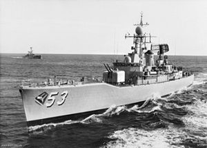 "Black-and-white photograph of a destroyer escort with the number ""53"" painted on the bow. The ship is underway. A second ship of a similar design is in the background."