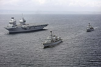 HMS Queen Elizabeth (R08) - Queen Elizabeth at sea on 28 June, two days after her departure from Rosyth, in company with frigates Sutherland (foreground) and Iron Duke (background)