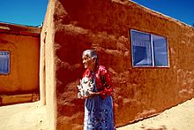 Helen Cordero standing by an adobe building in 1986