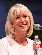Upper torso of a female wearing white shirt. She is seen with a microphone and a plastic bottle in front of her.