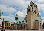 A romanesque stone cathedral, view of the north side. The green copper dome over the transept crossing is visible.