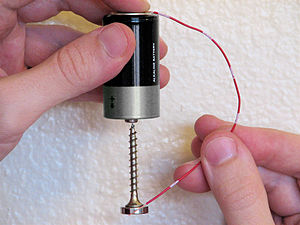 Homopolar motor - DIY simple homopolar motor made with a drywall screw, a battery cell, a wire, and a disk magnet. The magnet is on top of the screw head. The screw and magnet make contact with the bottom of the battery cell and are held together by the magnet's attraction. The screw and magnet spin, with the screw tip acting as a bearing.