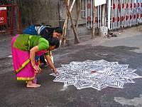 Women drawing an intricate kolam outside the Mylapore Temple