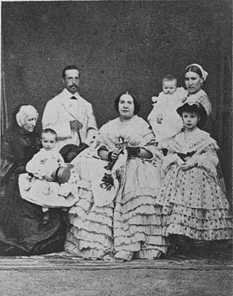 Isabella, Princess of Asturias (1851–1931) - Infanta Isabella, age eight, with her family. From left to right:  The Marchioness of Malpica with Alfonso, Prince of Asturias, on her lap; Francis, Duke of Cádiz, Queen Isabella II of Spain, and their royal wet nurse holding Innfanta María de la Concepción, and Infanta Isabella. 1860.