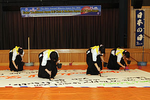 Four female Japanese high school students wearing hakama write calligraphy on a large sheet of paper fixed to the floor. The sheet is around five meters wide and three meters high.