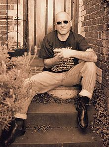 Man sitting on back door steps, wearing jeans, boots, black T-shirt and sun glasses. Rests left elbow on left knee with left forefinger pointing to his right. Right fist hidden inside left hand and he is facing forward.