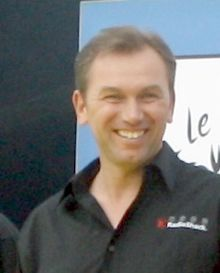 A smiling man in his forties wearing a black polo shirt with a wide lapel.