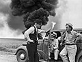 John Butler talks with two men while oil well fire burns in background (9238328229).jpg