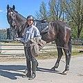Jonge vrouwelijke amazone met haar zwarte paard.jpg