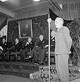 Jongen staand voor een microfoon, op de achtergrond een groep mannen zittend on…, Bestanddeelnr 255-8531.jpg