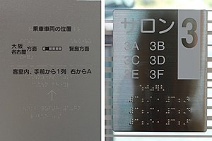 Japanese Braille - At left, Japanese print and braille text.  The embossed text includes non-braille lines, bullets, and an arrow. At right, an illustration of Western digits and letters.