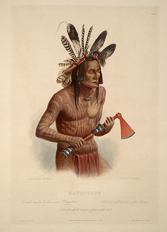 """Mato-tope - Mato-Tope, Adorned with the insignia of his warlike deeds.: aquatint by Karl Bodmer from the book """"Maximilian, Prince of Wied's Travels in the Interior of North America, during the years 1832–1834"""". The six sticks in his hair represent killing six men with a gun and the wooden knife represents he killed a Cheyenne chief with a knife. The split turkey feather is said to stand for an arrow wound. The hand on Four Bears' torso may indicate that he once seized an enemy for his comrades to kill."""