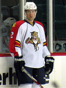 A Caucasian ice hockey player standing relaxed on the ice. He wears a white, visored helmet and a white and orange jersey. He holds his stick on the ice lightly with one hand.