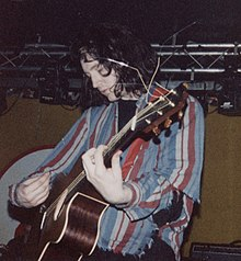 A man performing live on-stage with an acoustic guitar.