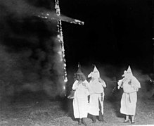 Three men in white robes and hoods standing in front of a large burning cross.