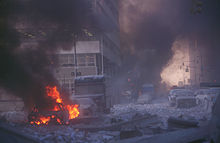 Street level photograph showing fire, debris, smoke and ashes.