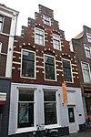foto van Pand met trapgevel met natuurstenen banden en blokken. Tudorbogen boven vensters