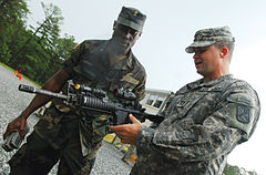 A colour photograph of two soldiers, one holding an assault rifle, talking at a training ground. The soldier on the left is in a camouflage field uniform, while the soldier on the right holding the rifle is in a grey camouflage uniform