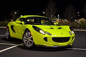 A green Lotus Elise at night.