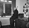 Man met een pijp staat tegen een bureau geleund voor het raam te roken, Bestanddeelnr 252-9126.jpg
