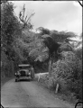 Motor car with Albert Percy Godber's wife, Laura Godber, and one of his grandsons standing in front of a car parked on a bend on the Akatarawa Road, circa late 1930s or early 1940s ATLIB 308051.png