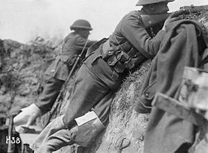 A black and white photograph of two men in military uniform pointing rifles over the lip of the trench in which they are standing