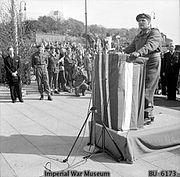 Man standing at podium with a crowd behind