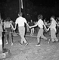 Op straat dansen mensen in een kring terwijl ze elkaars handen vasthouden, Bestanddeelnr 255-1923.jpg