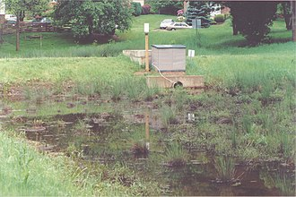 Media filter - Peat-sand filter in United States. The filter treats stormwater runoff from a residential area.  Stormwater from streets is first routed to a small detention basin (rear of photo, behind berm), which removes coarse sediment. After filtration an under-drain piping system discharges the filtered water to an adjacent stream.