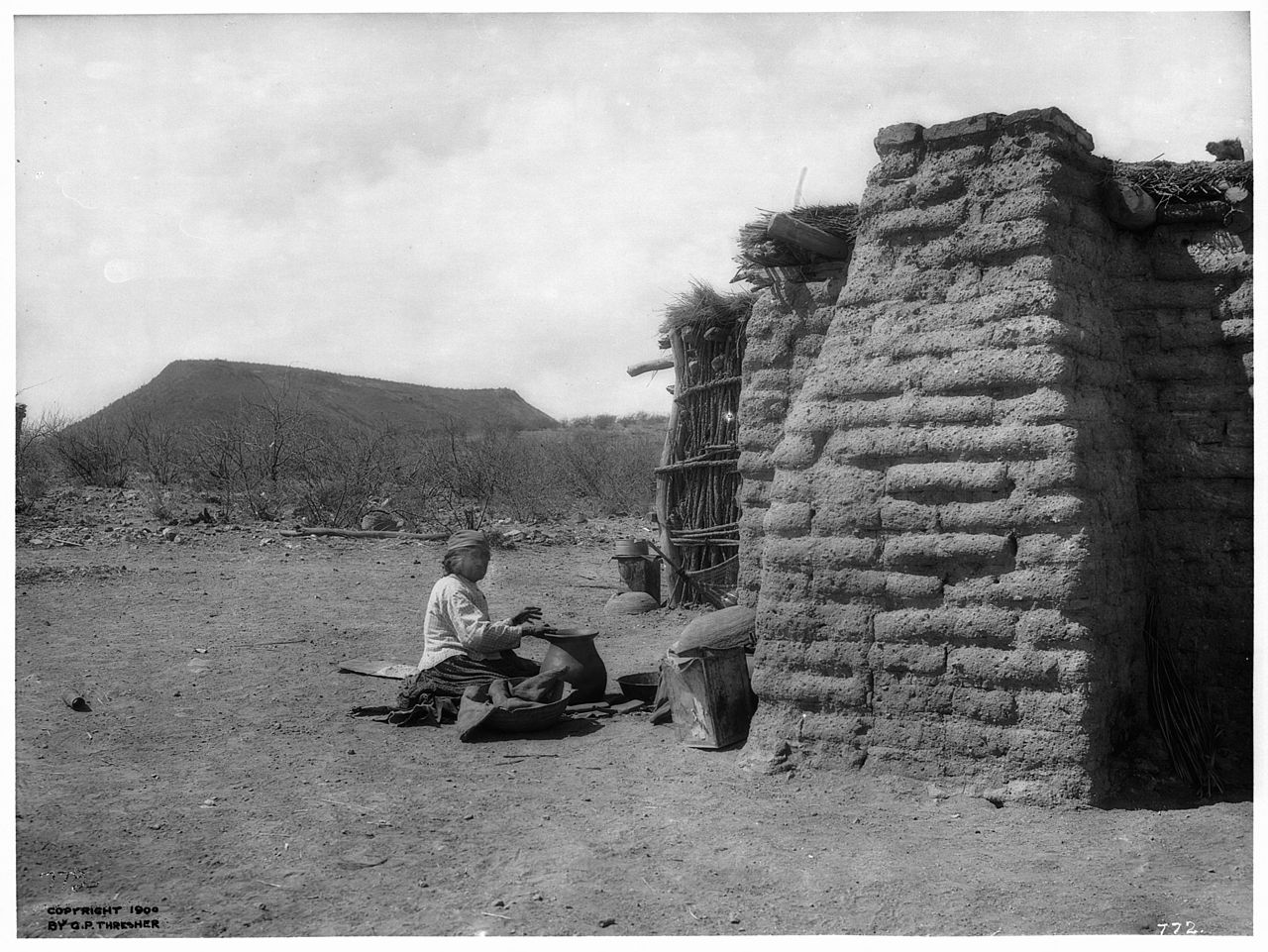 file pima indian woman sitting on the ground making pottery by an adobe and grass hut  gila