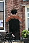foto van Poortje. Geprofileerd gemetseld rondboogpoortje van geslepen steen. Boven poortje ovaal venster met smeedwerk