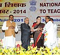 Pranab Mukherjee presenting the National Award for Teachers-2014 to Smt. Laxmi Uike, Chhattisgarh, on the occasion of the 'Teachers Day', in New Delhi. The Union Minister for Human Resource Development, Smt. Smriti Irani.jpg