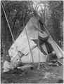 Rabit and his wife from Pine Point sit in front of teepee - NARA - 285216.tif