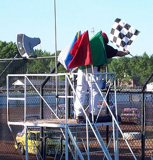 Racing flags - The flagman displaying the chequered flag with a complete set of stockcar racing flags