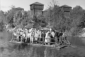 Rivers of America (Disney) - Disneyland guests take a raft to Tom Sawyer Island, about 1960