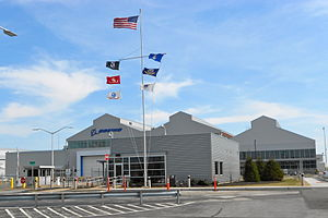 Boeing plant in Ridley Park, Pennsylvania – a building with aluminum siding, parking lot in front, and a flagpole with seven flags