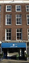 foto van Pand met drie verdiepingen. Rijk geprofileerde houten kroonlijst waaronder fries met panelen. Winkelpui uit de bouwtijd