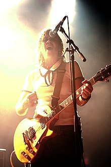 A Caucasian female with shoulder-length brown hair wearing a white shirt and dark pants sings into a microphone while strumming a yellow electric guitar.