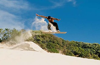 Sandboarding - A sandboarder does a jump on Fortaleza dunes.