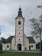 Photo depicts a white stone church with a tall square tower topped by an onion dome.