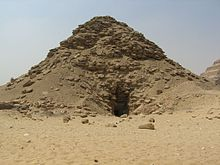 Ruined pyramid with a deep black depression at the center of the base of the pyramid.